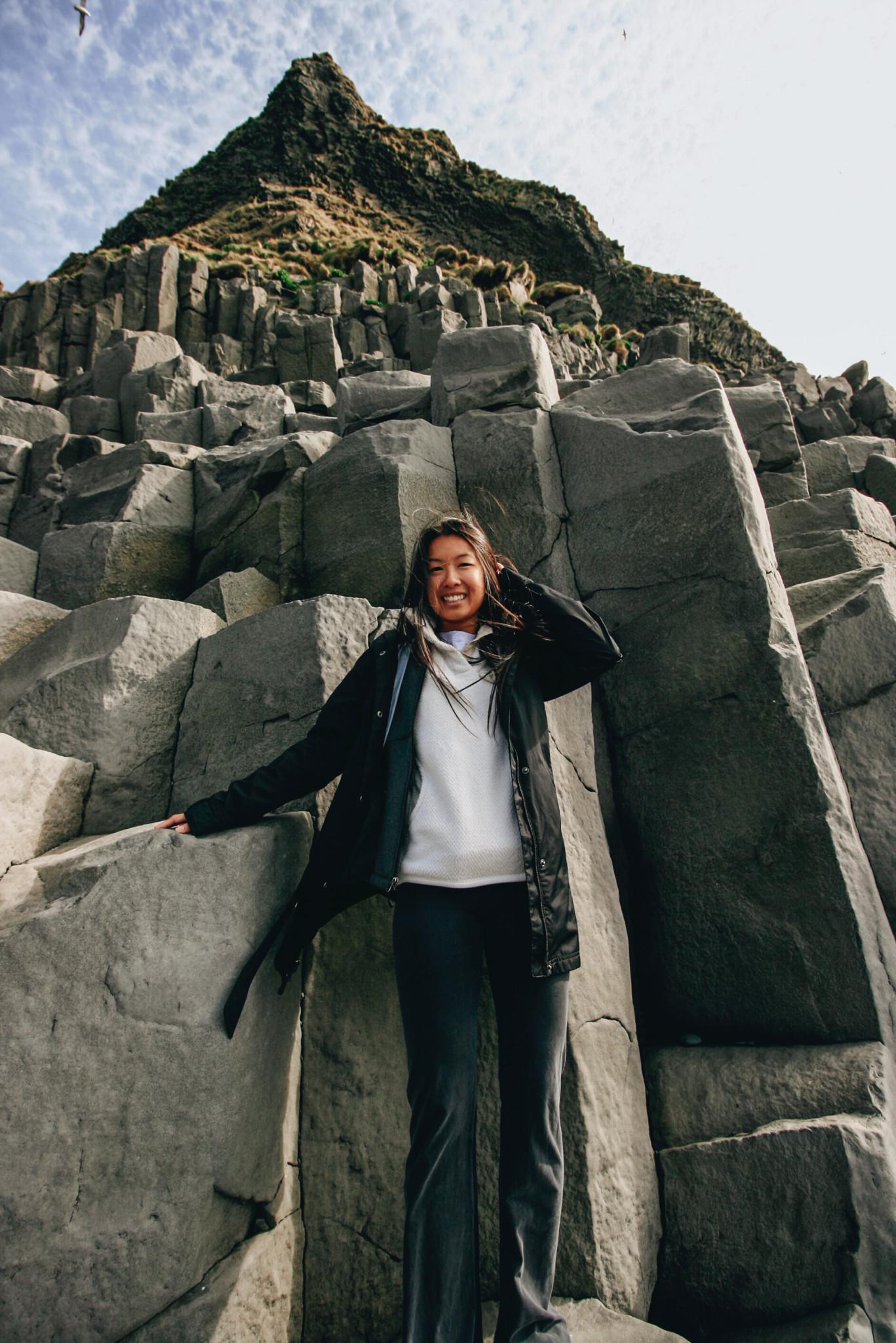 Posing with Basalt Columns on Black Sand Beach in Reynisfjara, Iceland