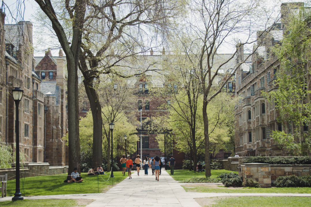 Students walking through gateway of Yale University in New Haven, CT