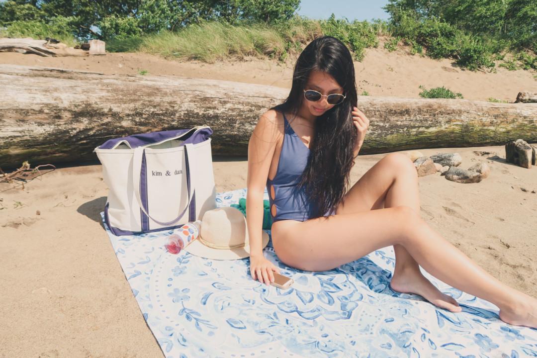 Girl in purple bathing suit posing on beach